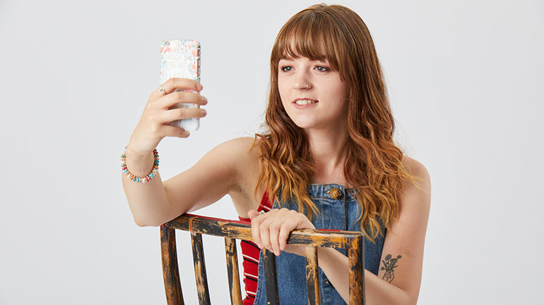 Seren, a young cancer patient CLIC Sargent supported, holding her mobile phone