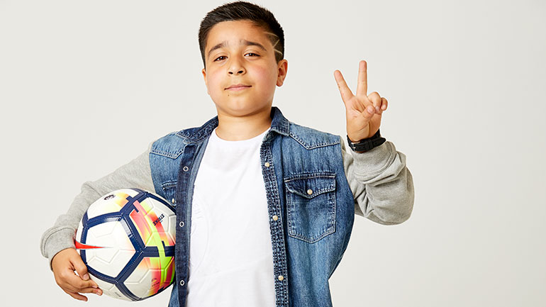 Sofyan, a young cancer patient, holds a football